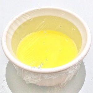 Egg whites in a ramekin wrapped with plastic wrap with a few holes punched in.