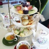 Afternoon tea served in floral tea ware and teapots on tea warmers.