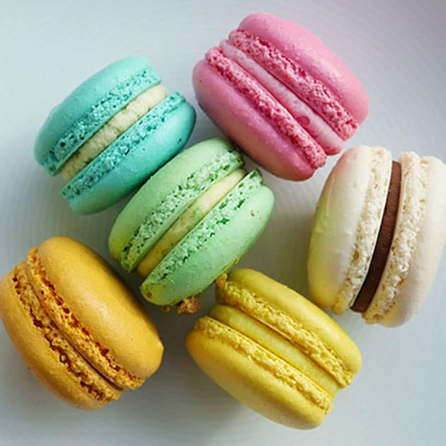 A plate filled with round and smooth macarons with no bumpiness.