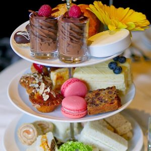 A traditional selection of afternoon tea items on a 3-tier porcelain serving tray.