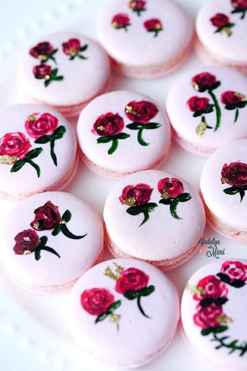 Pink hand painted floral macarons on a plate.