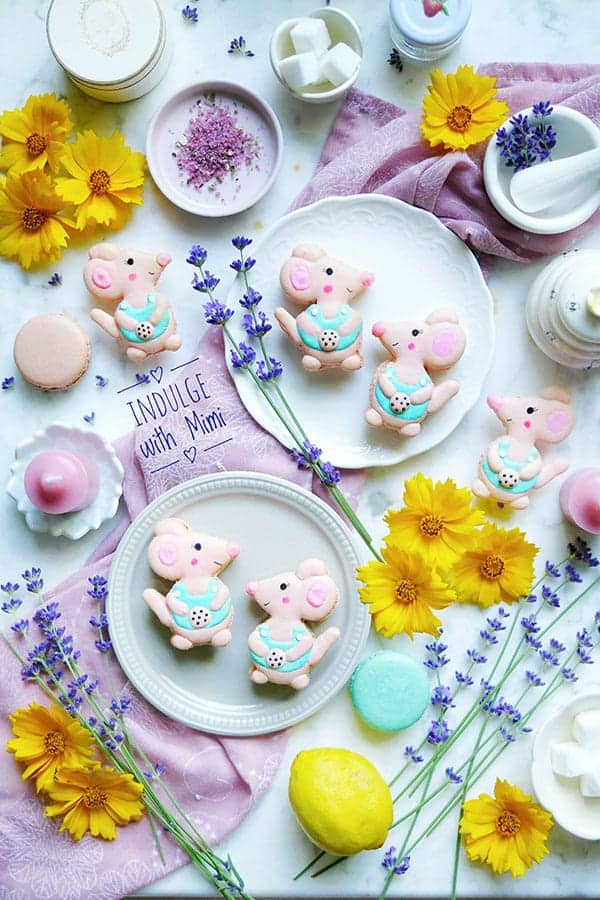 Mouse macarons on a counter with lavender, lemons and other ingredients.