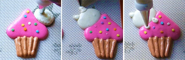 piping the head of the kitty onto macaron design.