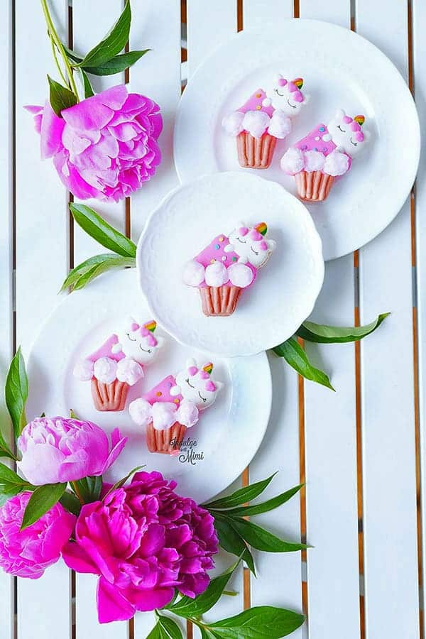 unicorn macarons on a plate with flowers.