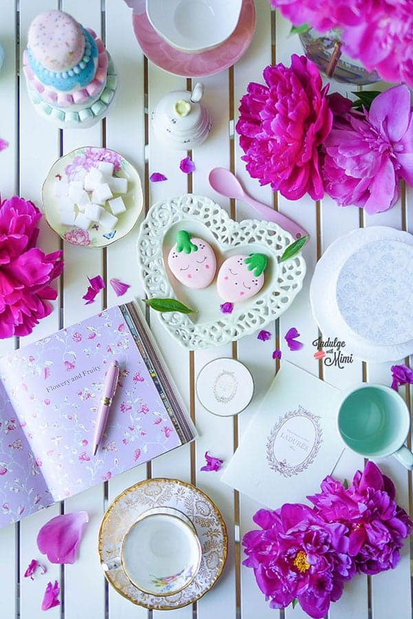 Overhead shot of strawberry macarons with tea ware and stationary.