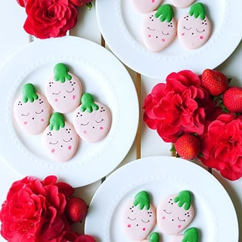 Strawberry shaped macarons on 3 different plates.