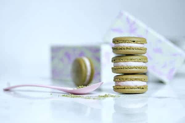 Stack of matcha strawberry macarons on a counter with some loose green tea powder.