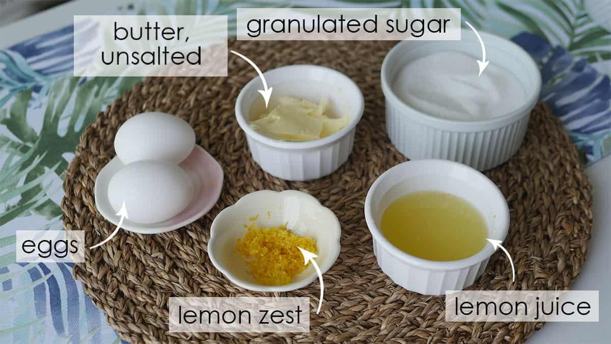 Sugar, lemon juice, lemon zest, eggs and butter sitting on a placemat.