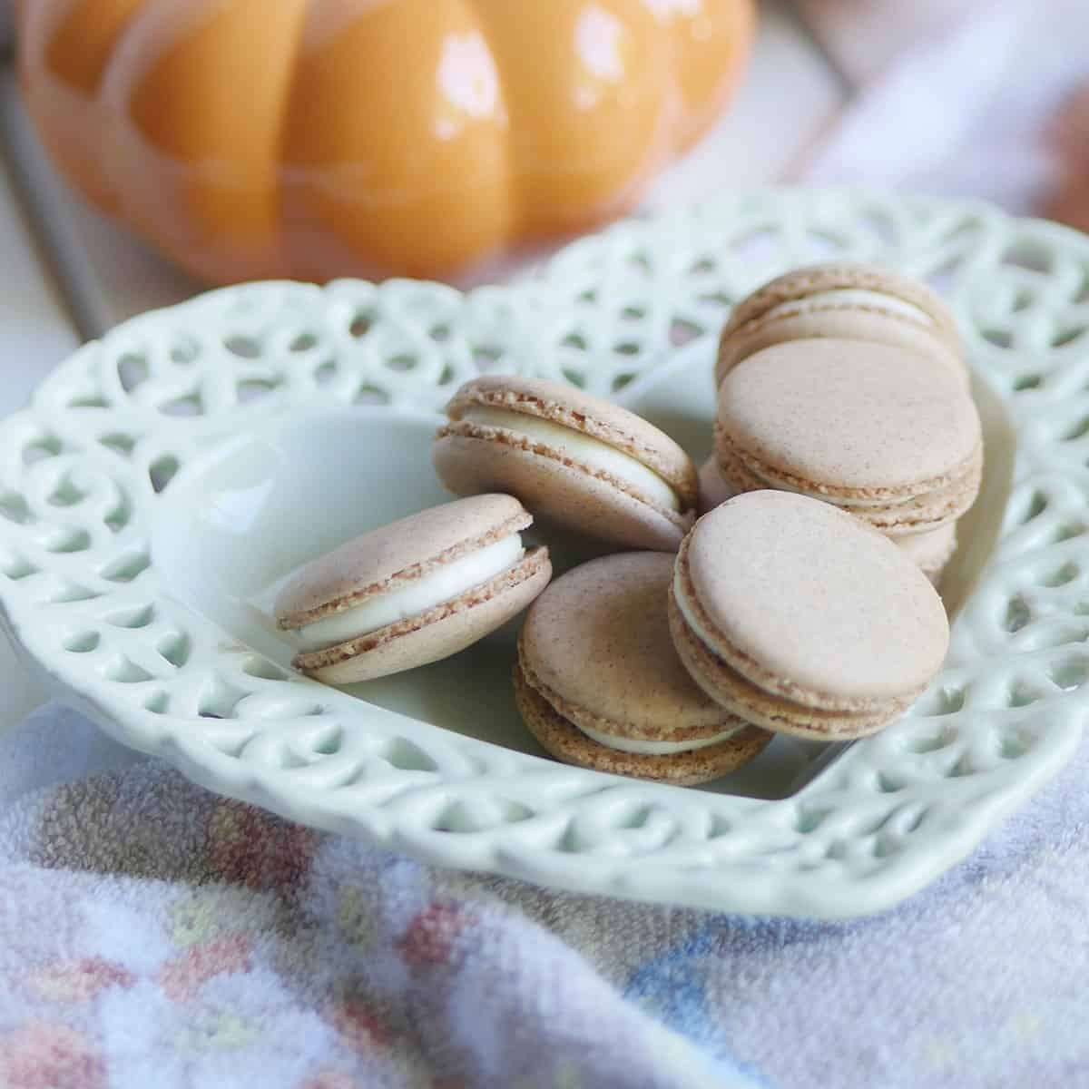 Pumpkin spice macarons on a heart shaped plate with pumpkin
