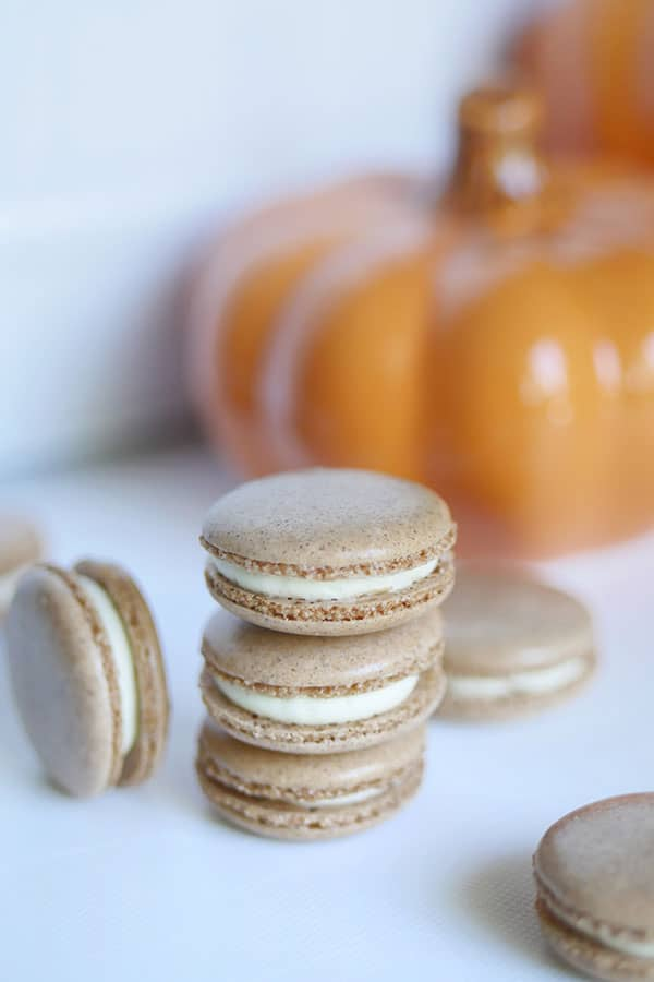 A stack of pumpkin spice cheesecake macarons in front of a pumpkin.