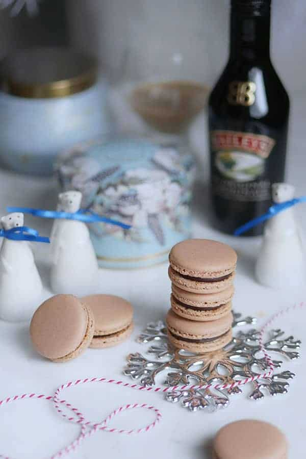 Baileys macarons in a stack styled with mini polar bear figurines and a bottle of Baileys Irish Cream.