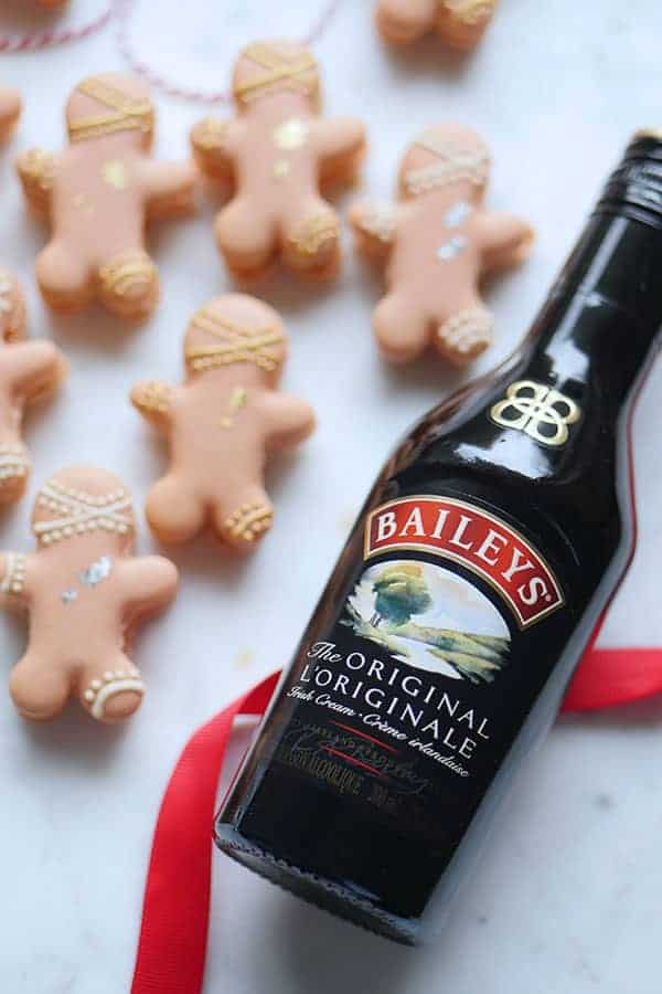 Close up of Baileys liqueur bottle with gingerbread man macarons in the back.