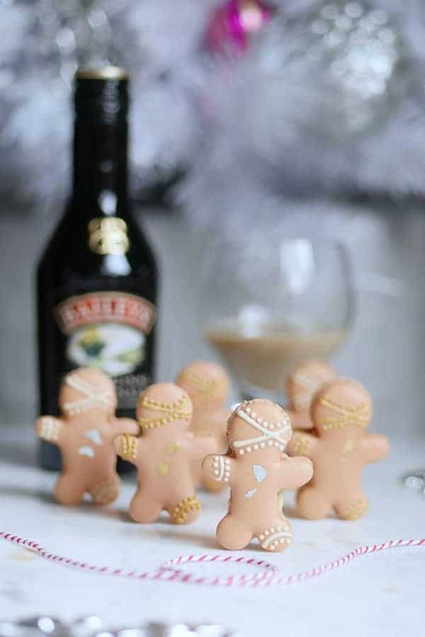 Gingerbread man macarons standing with a bottle of Baileys Irish Cream in the back.