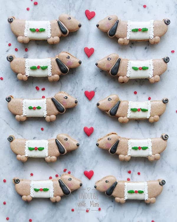 Dachshund wiener dog macaron in ugly Christmas sweaters facing each other with a heart sprinkle in between.