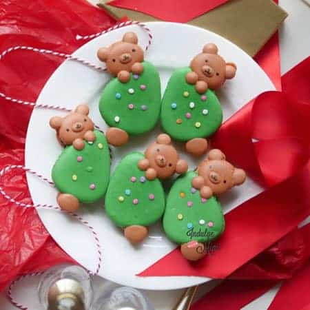 Christmas bear macarons hanging onto a Christmas tree.