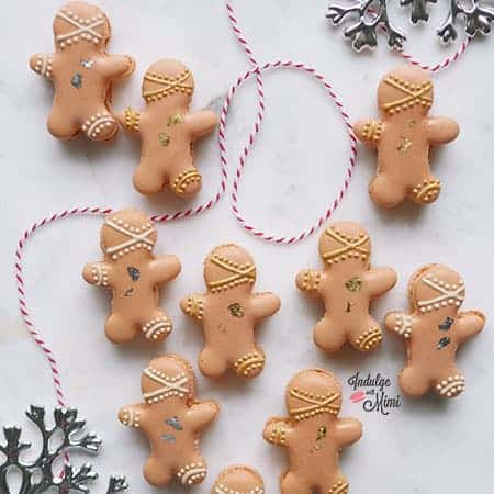 Gingerbread man macarons on a light marble counter.
