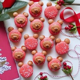 Christmas bear macarons with a holiday greeting card and holly on a white background.