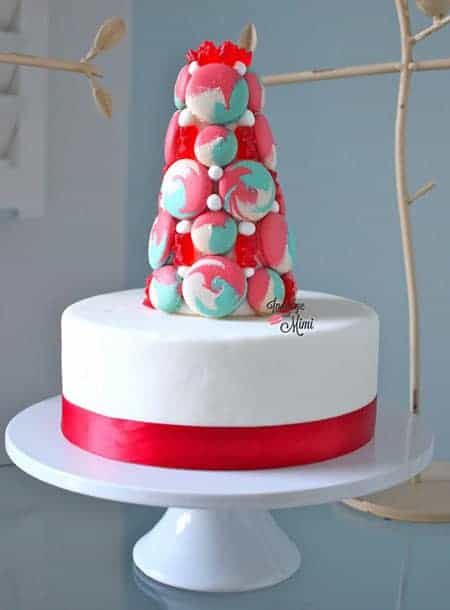 A festive holiday cake with a macaron tower on top.