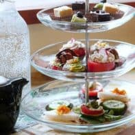 Vegan afternoon tea treats served on a clear glass 3-tier tea tray.