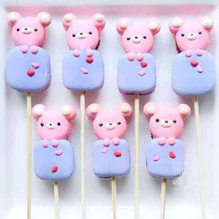 Bears on puffy block marshmallow shaped macarons on a lollipop stick.