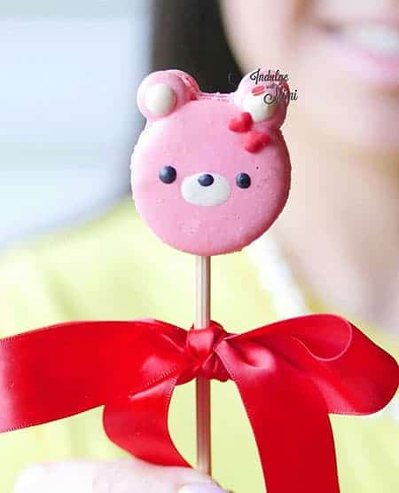 Bear on lollipop stick with hearts on side of his face.