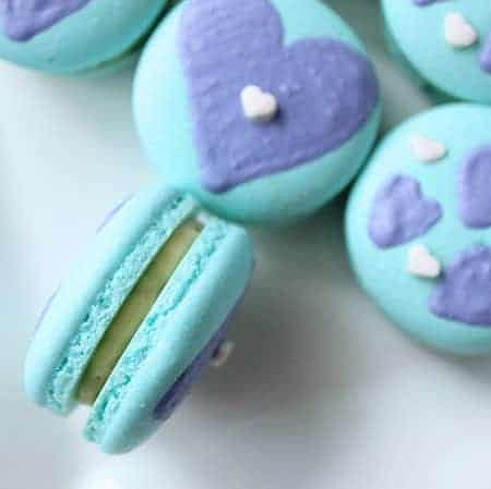 Side profile of Valentine's Day macarons showing dainty small macaron feet.