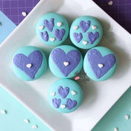 Turquois macarons with hearts piped on top.