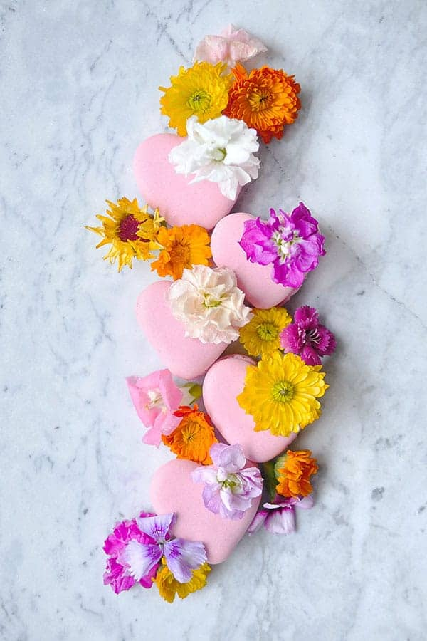 Heart macarons on marble topped with edible florals.