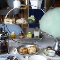 Afternoon tea sweets and savouries served on a silver open book shelf display.