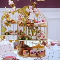 Afternoon tea treats displayed in a bird's cage display.