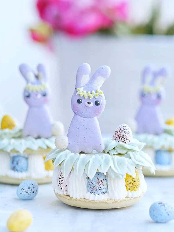 Easter bunny perched on top of a big macaron filled with easter eggs.