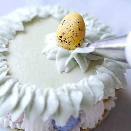piping buttercream leaves under easter egg.