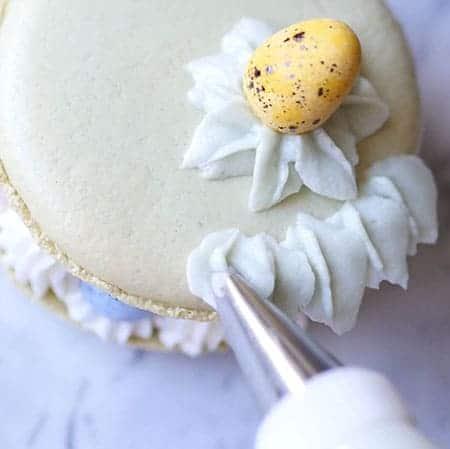 Adding buttercream leaves on the edge of big macaron.