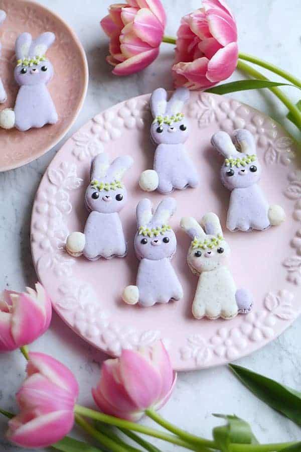 A bunch of bunny macarons on a plate surrounded by  flowers.