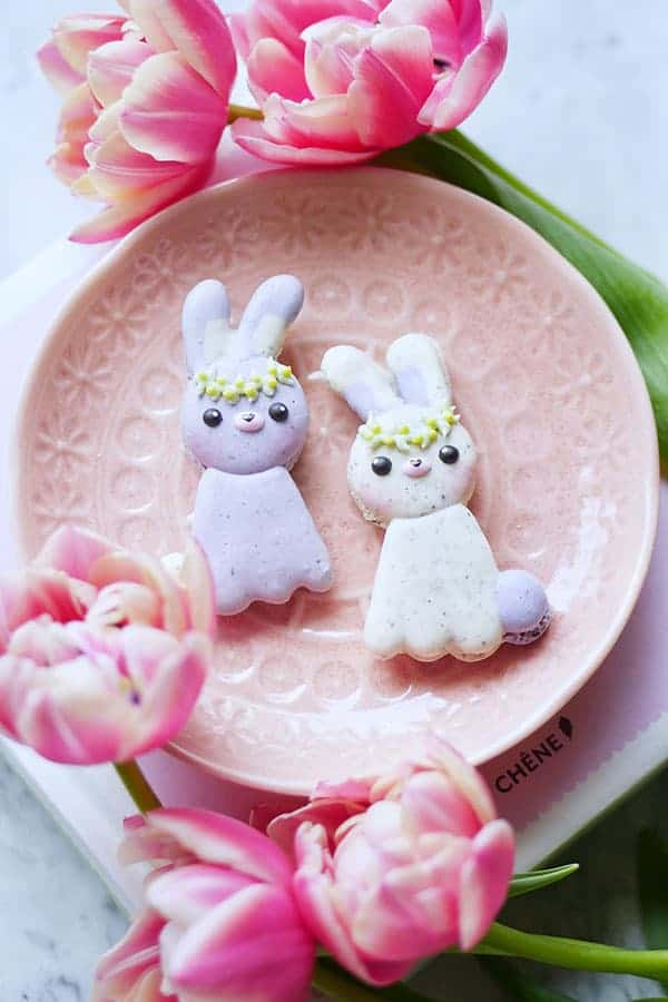 Naturally speckled lavender earl grey macarons in the shape of bunnies on a small plate.