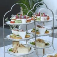 High afternoon tea items served on a sleek white 3 tiered tea tray.