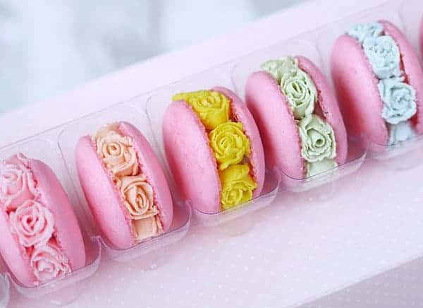 A box of macarons with buttercream flowers.
