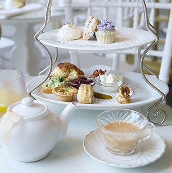A home-style afternoon tea set served on a 2 tier tea tray in a white farmhouse setting.