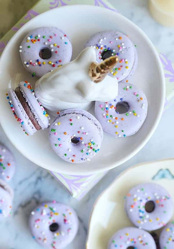 lavender donut macarons on a unicorn plate shot from above.