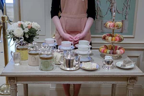 Server standing in front of Laduree tea cups.