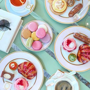 Macarons, croissants, lemon meringues and more served on pastel tea ware.