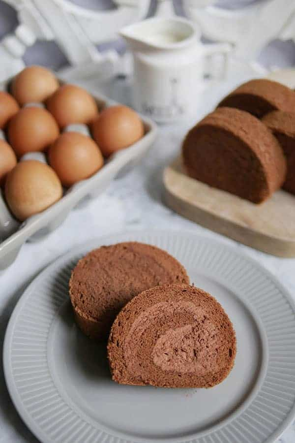Chocolate cake roll slices on a grey plate with eggs and a creamer in the back.