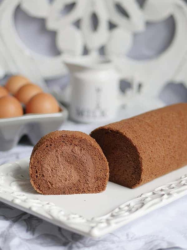A slice of chocolate cake roll shown from the side.