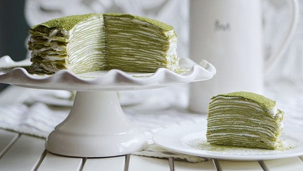Mille crepe cake on a cake stand with a piece on the side. Both shows 28 layers of crepes stacked to make mille crepe cake.