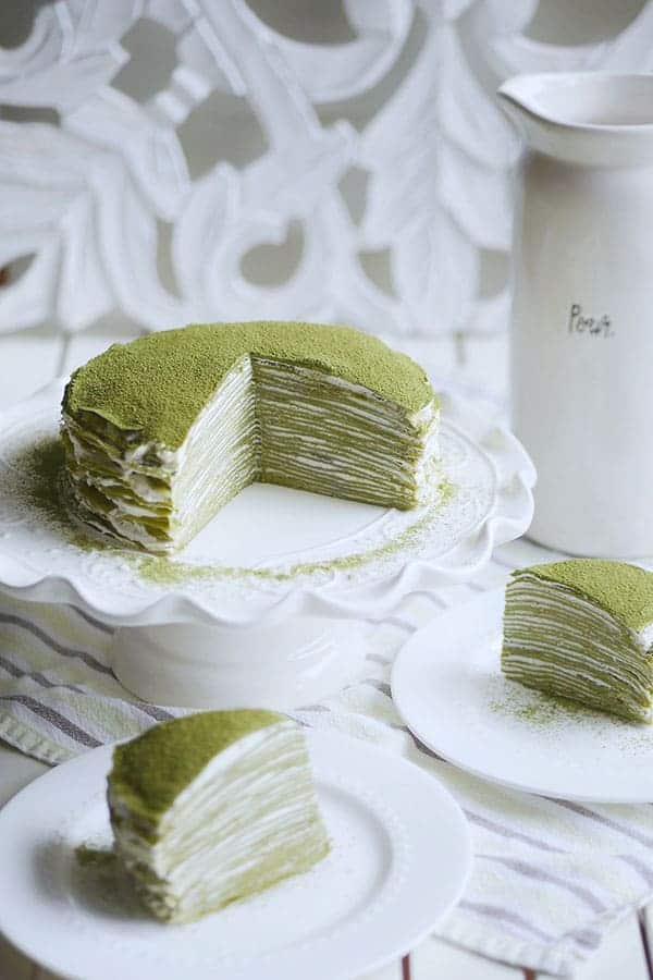 A whole matcha mille crepe cake cut open with 2 slices on the side.