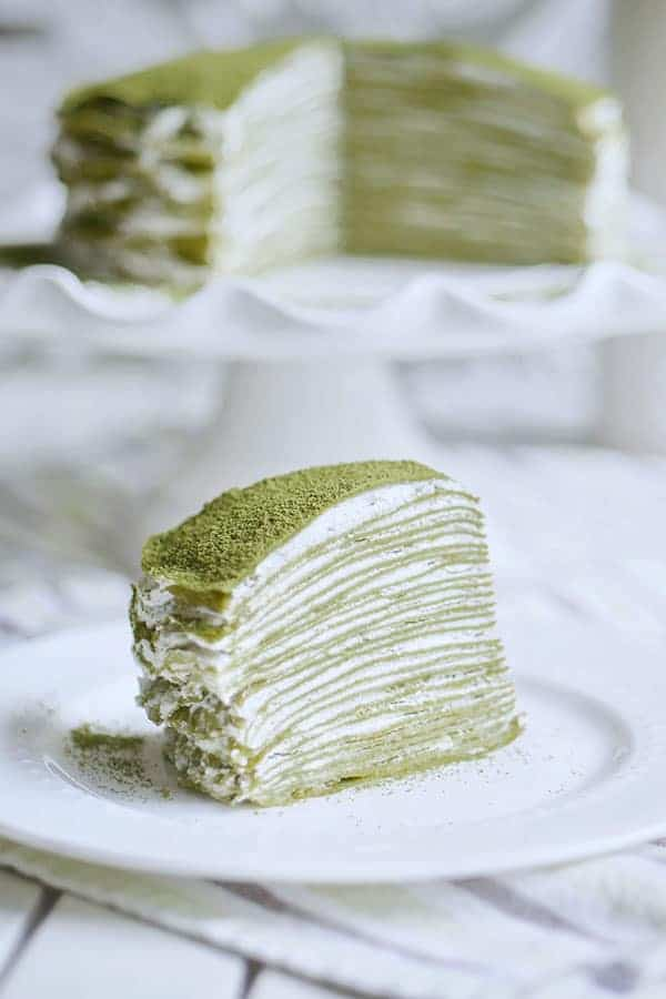 A close-up showing a cross section of a slice of 28 layer matcha mille crepe cake.