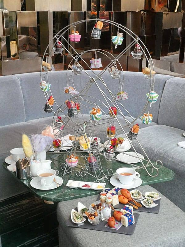 A large ferris wheel display is set on a low table with afternoon tea treats on it.