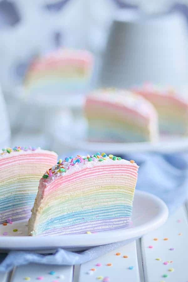 Close-up shot of rainbow mille crepe cake showing all 30-layers of the crepe with a thin layer of cream filling in between.