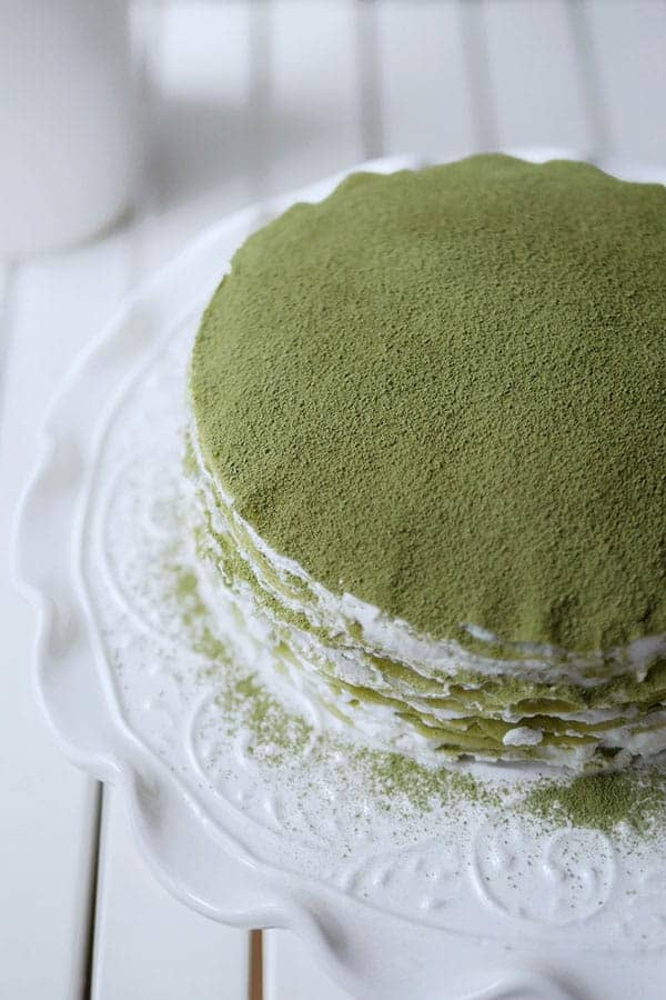 Top of a matcha crepe cake dusted with green tea powder.