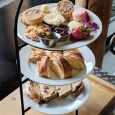 A 3-tier afternoon tea tray set on a table with desserts and treats.